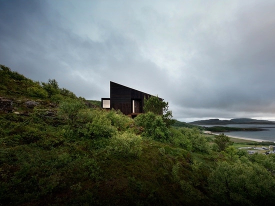 Stepping down the landscape from east to west, the timber cabin takes in sweeping views of the open sea on one side and the dramatic hills on the other. Large glazed openings and an all-timber pale...