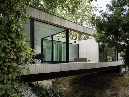 Spanning an impressive 210 feet, Bridge House crosses directly over a brook running through the property, marrying the landscape with minimal disturbance.