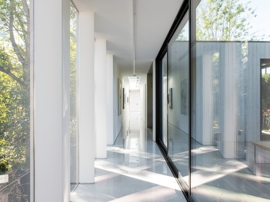 Doors and windows at the home's bridge filter and reflect light, with the overlapping patterns creating a dazzling display of ethereal beauty.