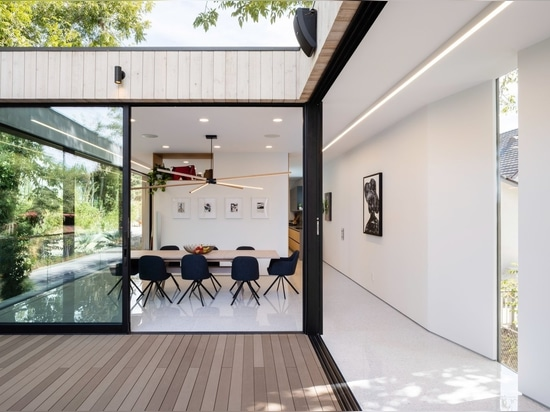 The courtyard, a dramatic indoor-outdoor experience, becomes an extension of the home's public space. Visual and functional connection to the dining room is enabled by Series 600 Multi-Slide Doors ...