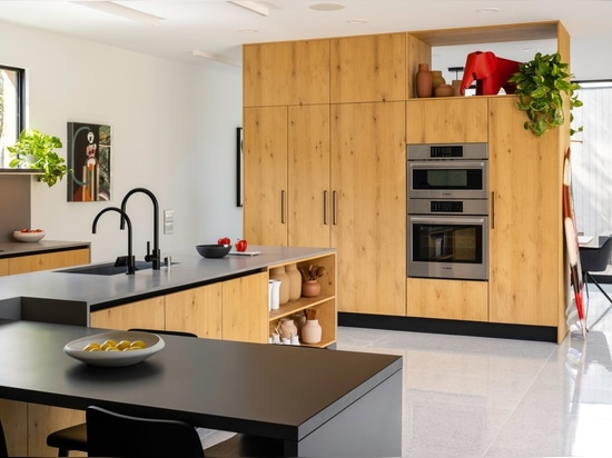 The warm and inviting kitchen occupies the space between the living and dining rooms, maintaining an open and fluid connection to both.