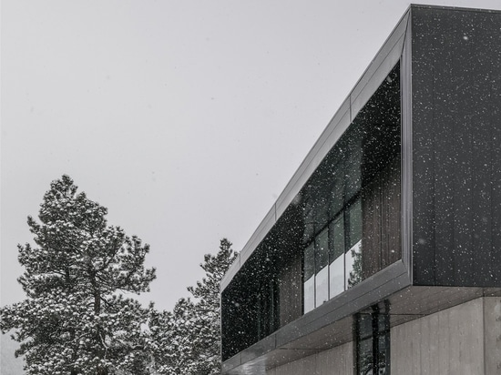 The upper facade features simple flush, glossy metal panels that reflect light and the landscape. This refined material contrasts with the raw-formed concrete podium that houses the lower level.