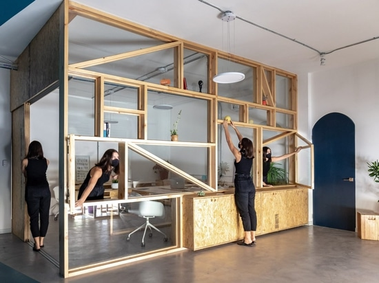 Pine-and-glass shelving encloses office in Ecuador