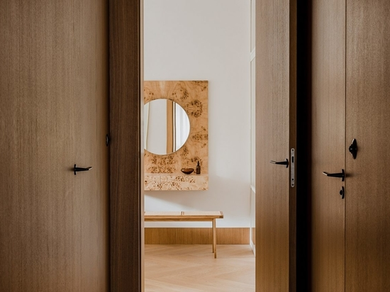 A wood-lined hallway leads to the apartment's master bedroom