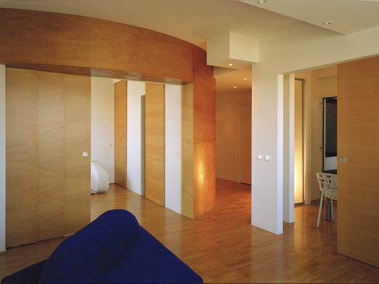 A wooden sliding door separates the living area from the sleeping quarters; the panels can be moved to transform the sleeping area into a single large space.   Read more: 1970's Roman apartment rec...