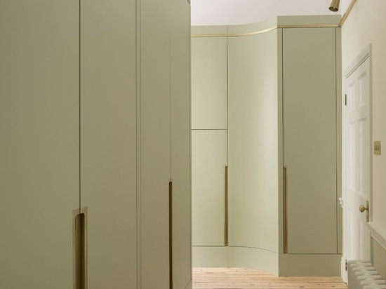 A small antechamber features pistachio-green storage walls