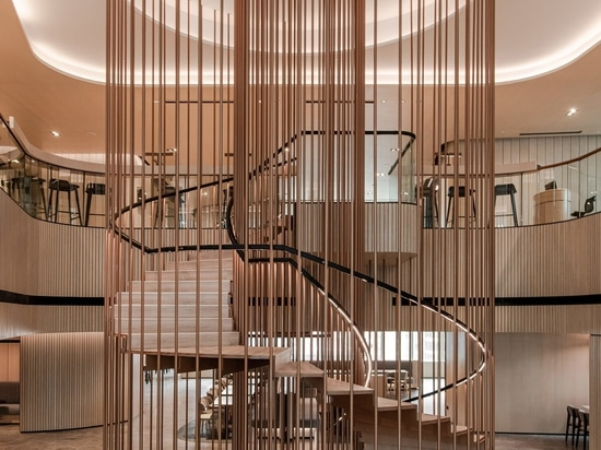 A central spiral staircase is enclosed by slatted bronze