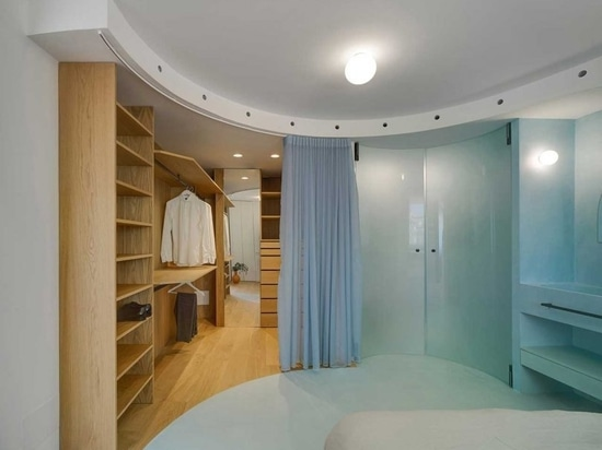 A curtain divider at the closet front and curved glass doors in the bathroom area follow the curved architectural element on the ceiling.