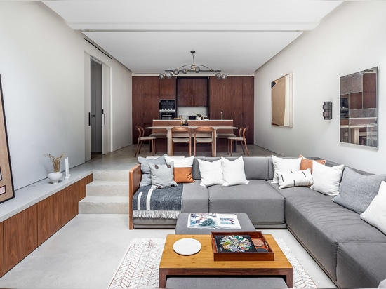 The basement level features a sunken seating area and a kitchen