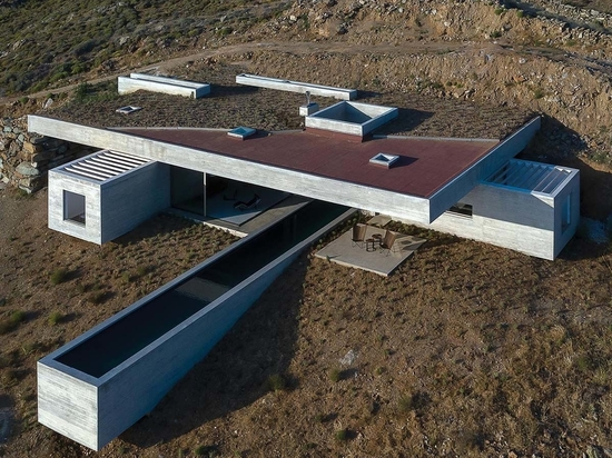 A Long Thin Swimming Pool Extends Out From This Hillside Home