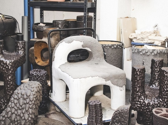 'Remolten N1: Monolita Low Chair 15' seen in progress, as a lava coating (the darker areas) is added to the stoneware form