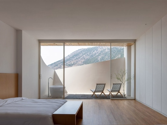 Floor-to-ceiling windows frame views across the mountains