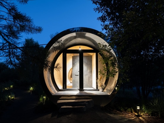 This Tube-Shaped Cabin With A Polished Metal Exterior Hovers Over The Surrounding Landscape