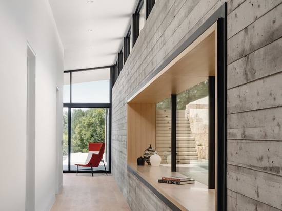 A hallway connecting the two living rooms provides a close-up look at the board-formed concrete wall and access to the bedrooms and bathrooms.