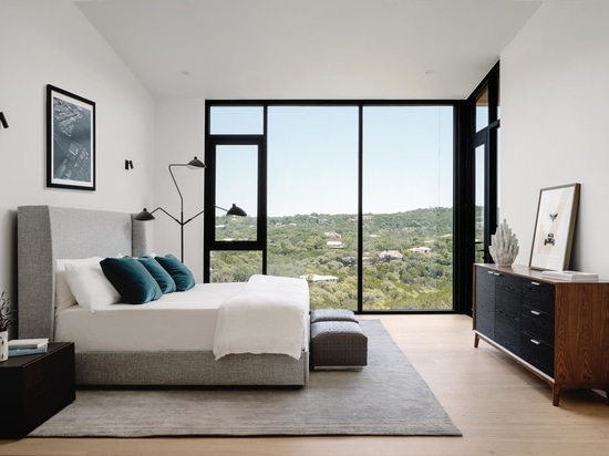 In one of the bedrooms, floor-to-ceiling windows allow the tree view to be enjoyed from the bed.