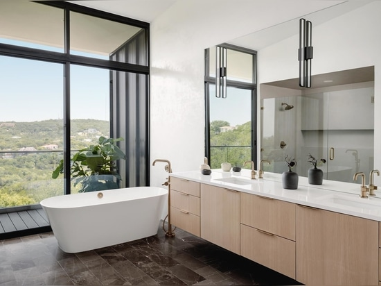 In one of the bathrooms, a mirror reflects the light and view seen through the large windows.