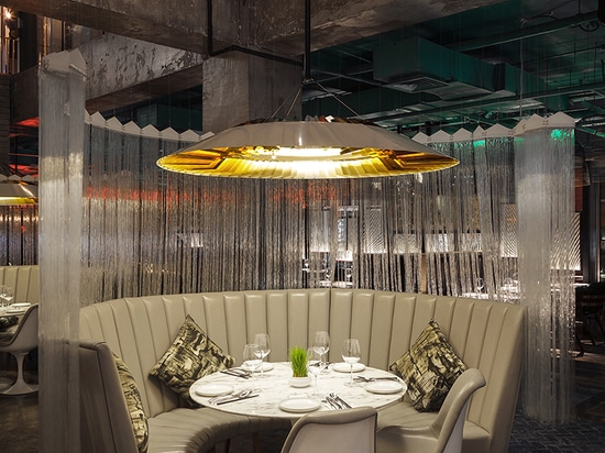 bespoke lights hover above the central dining booths, providing warm light diffused and reflected off 88 gold fins